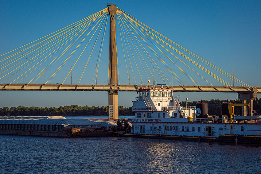 -barge-traveling-on-mississippi-river-near-cable-stayed-bridge.jpg