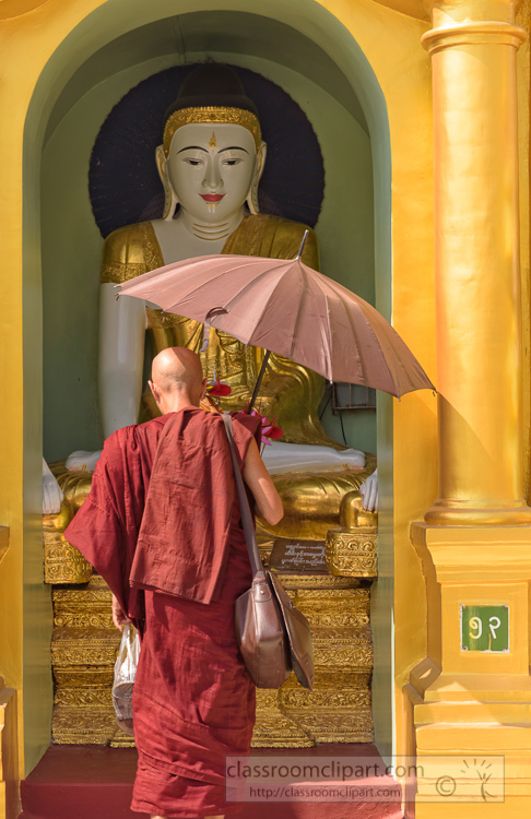 buddhist-monk-in-traditional-robes-holding-an-umbrella-at-shwedagon-pagoda-yangon-myanmar-6629E.jpg