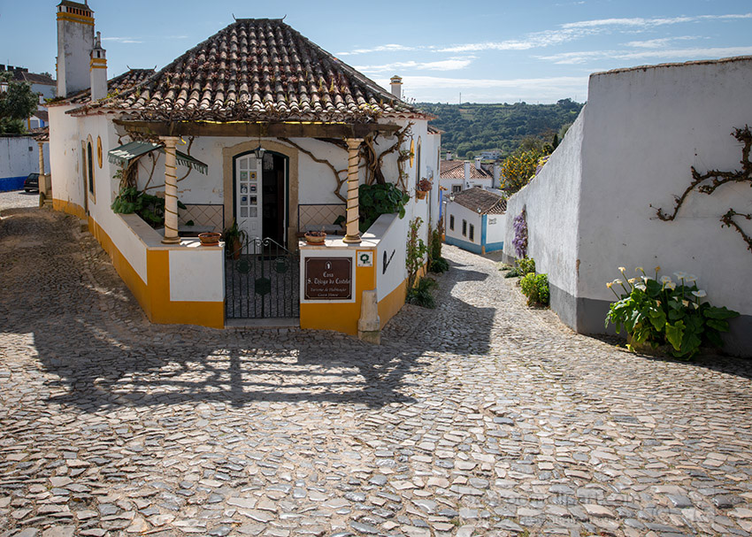 corner-building-alongg-cobble-stone-street-obidos-portugal.jpg