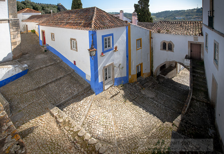 looking-down-at-white-washed-building-cobble-stone-street-obidos-portugal.jpg