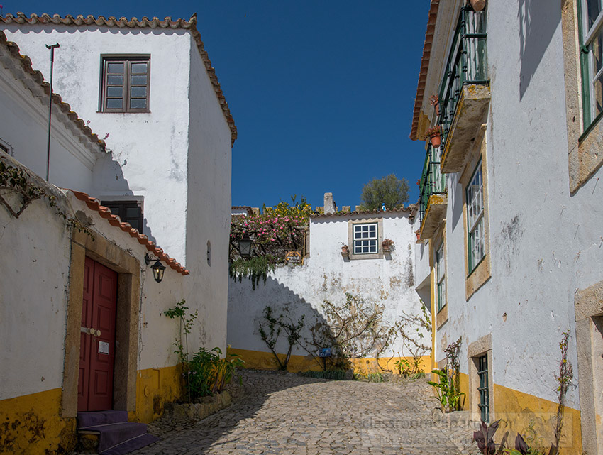 white-washed-yellow-trimmed-building-cobble-stone-street-obidos-portugal.jpg