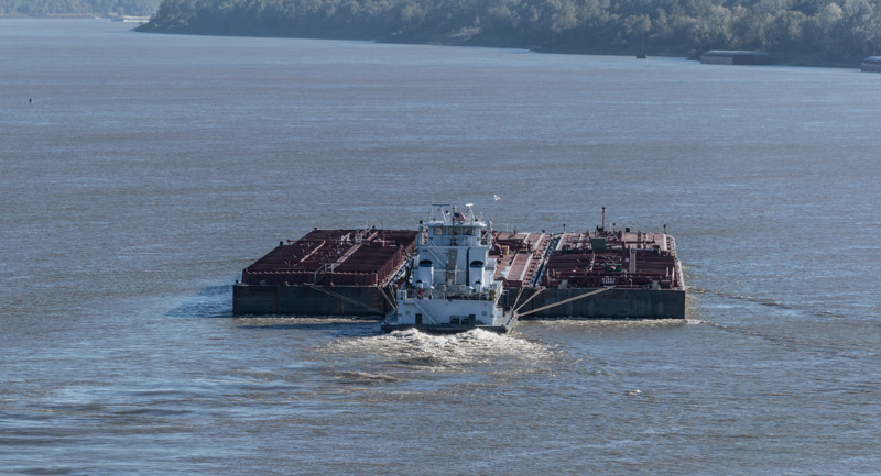 a-tugboat-pushes-a-wide-barge-upstream-on-the-mississippi-river-in-the-waters-between-tunica-county-mississippi-and-phillips-county-arkansas.jpg
