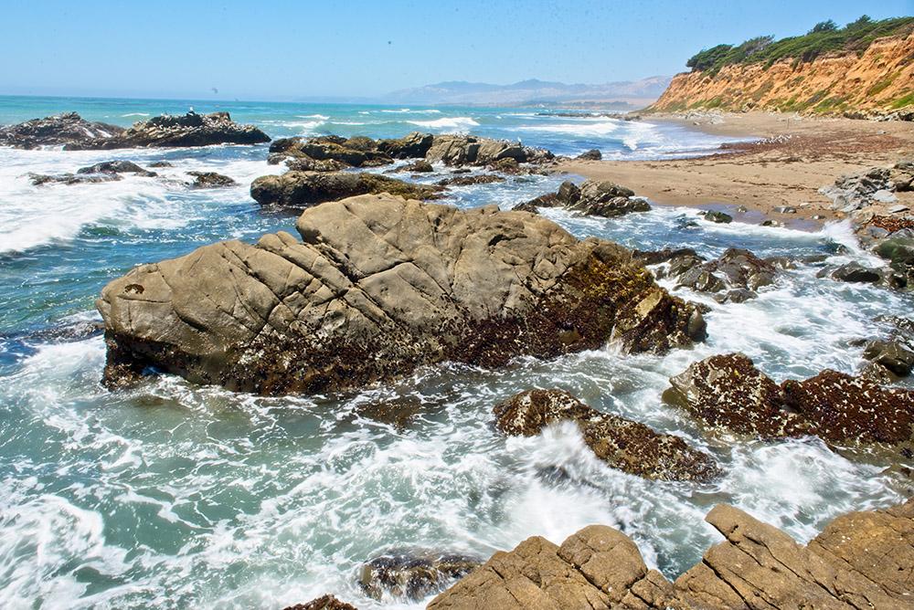 waves-breaking-on-a-rocky-shoreline-sunny-day.jpg