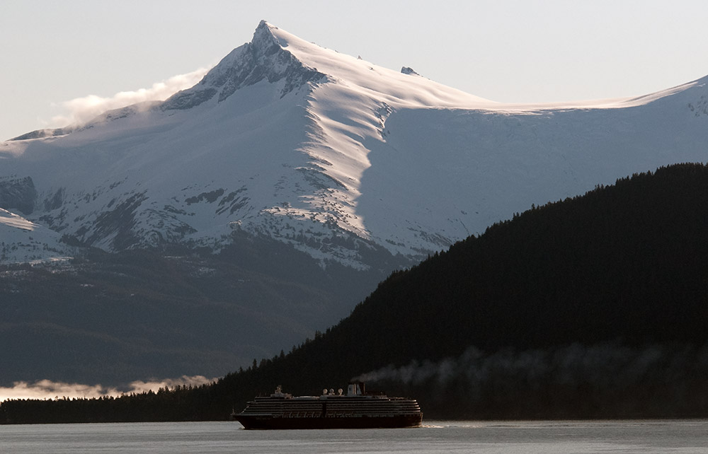 ship-sailing-in-the-waters-off-alaska-with-snow-covered-mountains-in-background.jpg