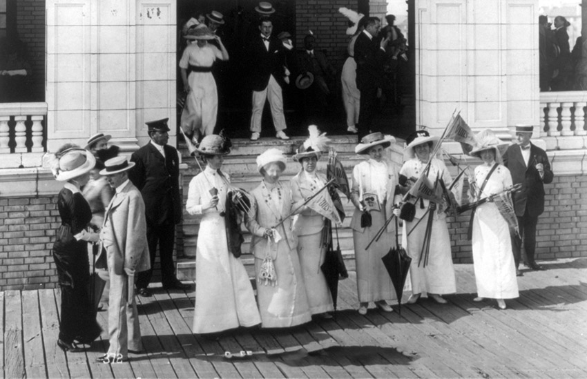 group-of-women-holding-banners-reading-votes-for-women-in-front-of-porch.jpg