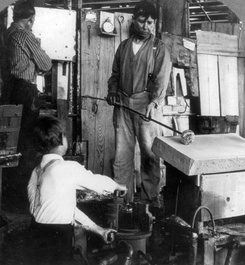 dipping-molten-glass-on-blowpipe-and-shaping-it-on-moulding-stone-1907.jpg