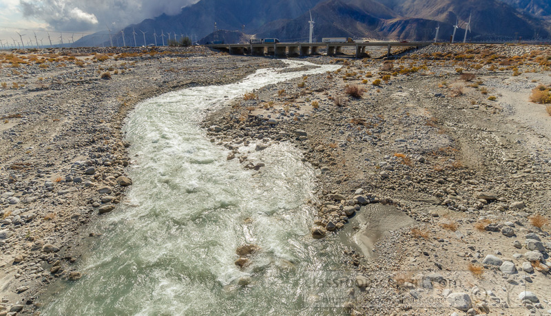 river-of-water-flowing-from-mountians-near-palm-springs-california-with-distant-freeway-.jpg