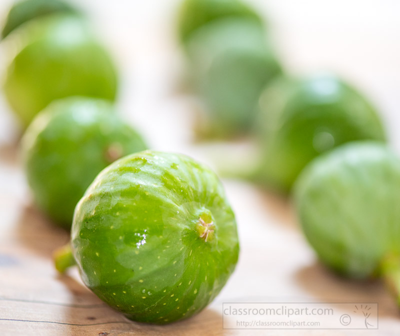 macro-closeup-rows-of-green-figs-on-wood-background.jpg