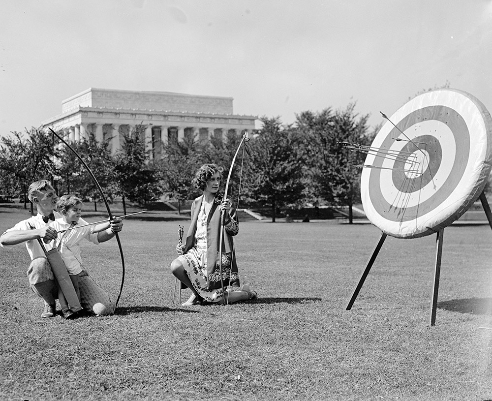 family-holding-bow-and-arrows-practicing-archery-1929.jpg