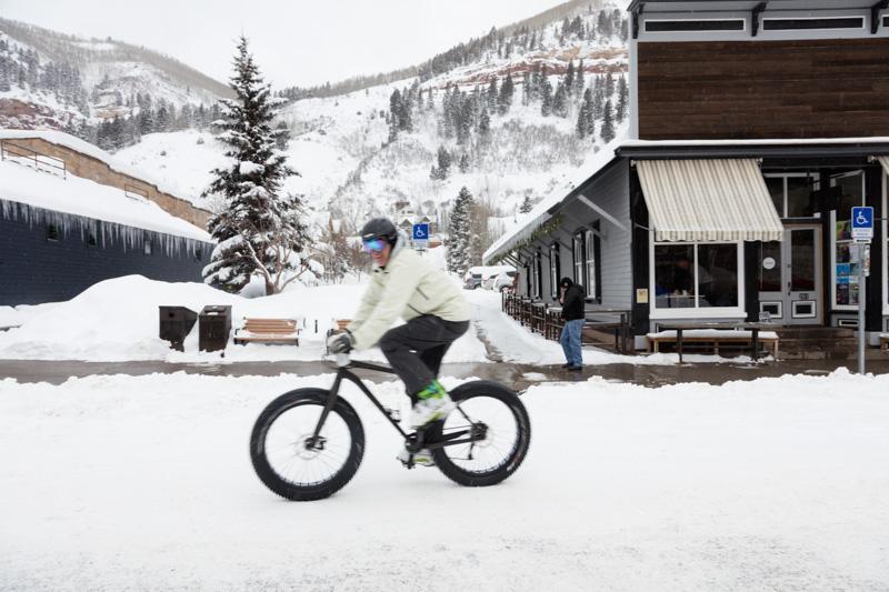 biker riding in heavy snow covers the main street of Telluride Colorado photo.jpg
