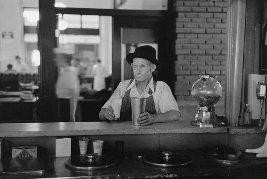 man-drinking-malted-milk-at-stand-in-streetcar-terminal-oklahoma-1939.jpg
