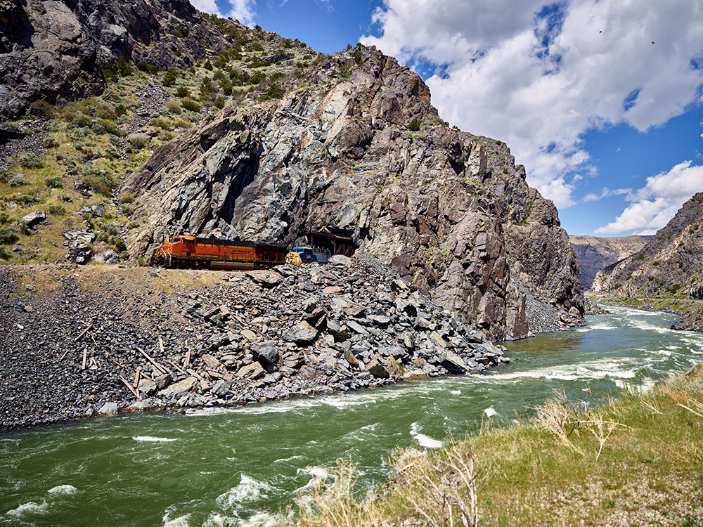 freight-train-emerges-from-a-tunnel-near-river-.jpg