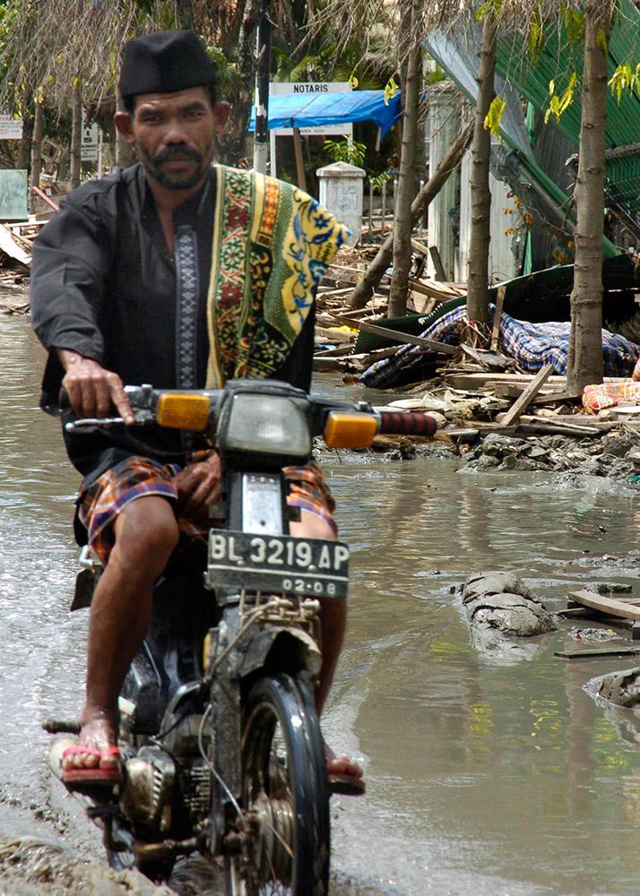 indonesian-man-rides-through-the-devastated-streets.jpg