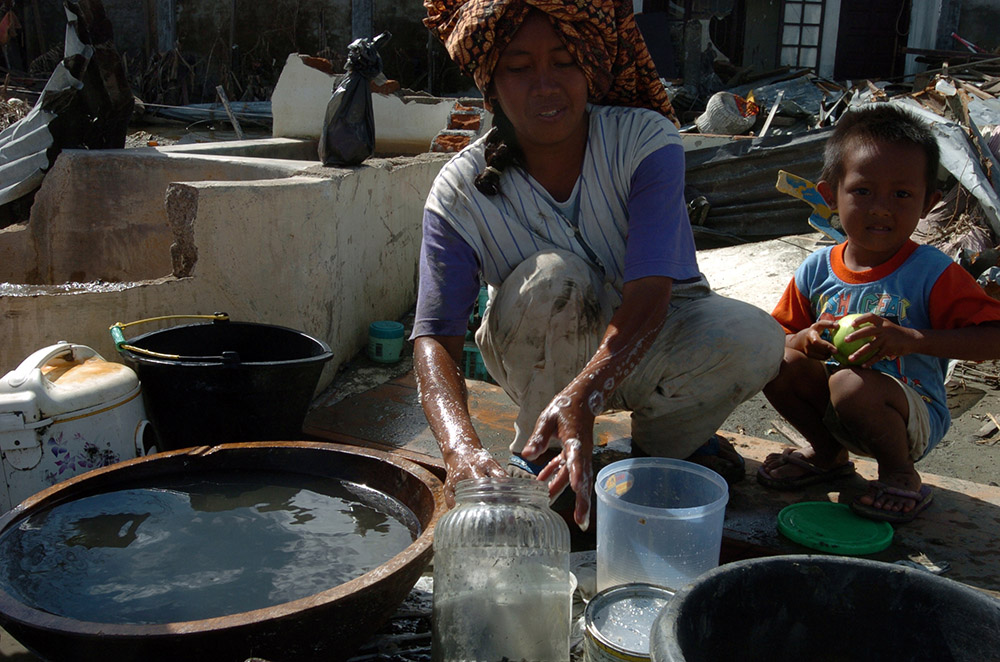 indonesian-woman-and-child-wash-dishes-amid-rubble.jpg