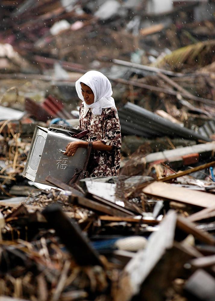 indonesian-woman-searches-through-debris-in-the-rain.jpg