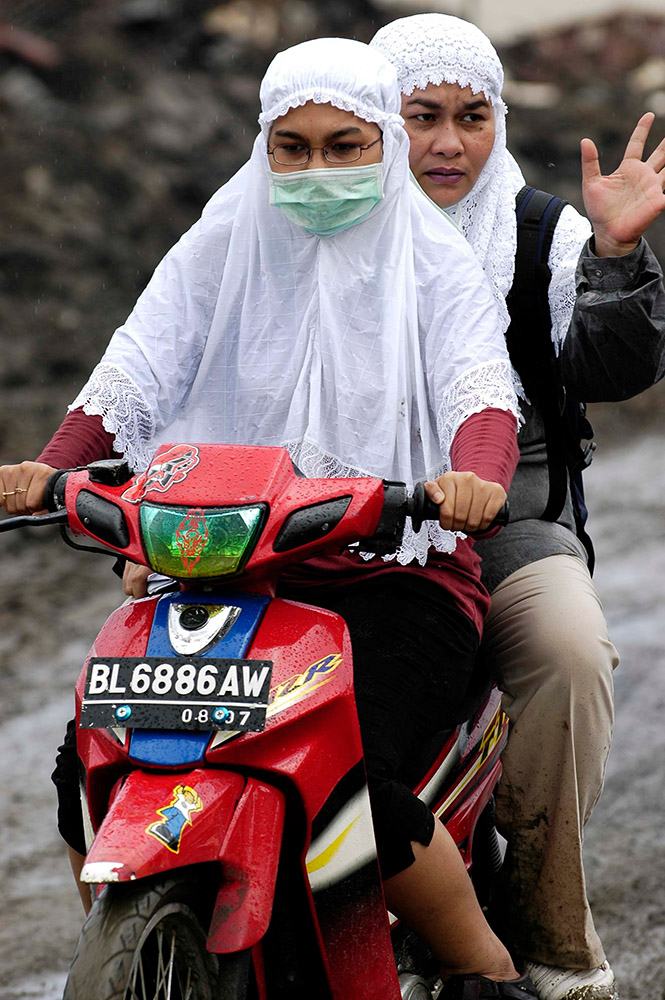 indonesian-women-on-a-motorcycle-ride-back-from-their-home-that-was-destroyed.jpg
