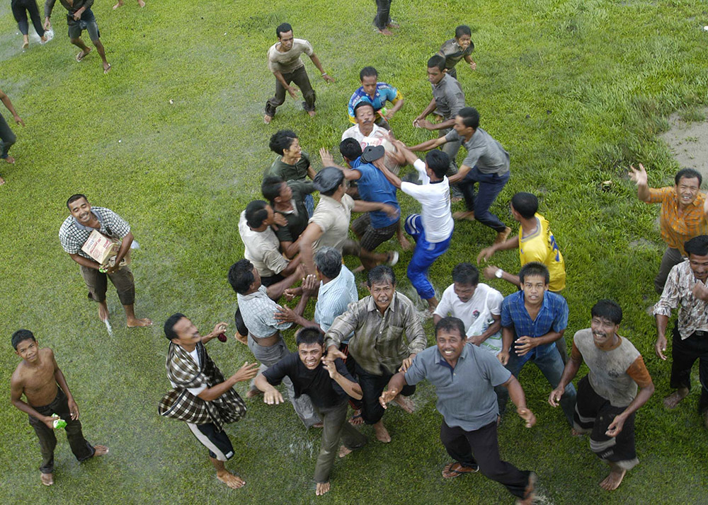 indonesians-from-a-small-village-reach-to-catch-supplies-from-helicopter.jpg