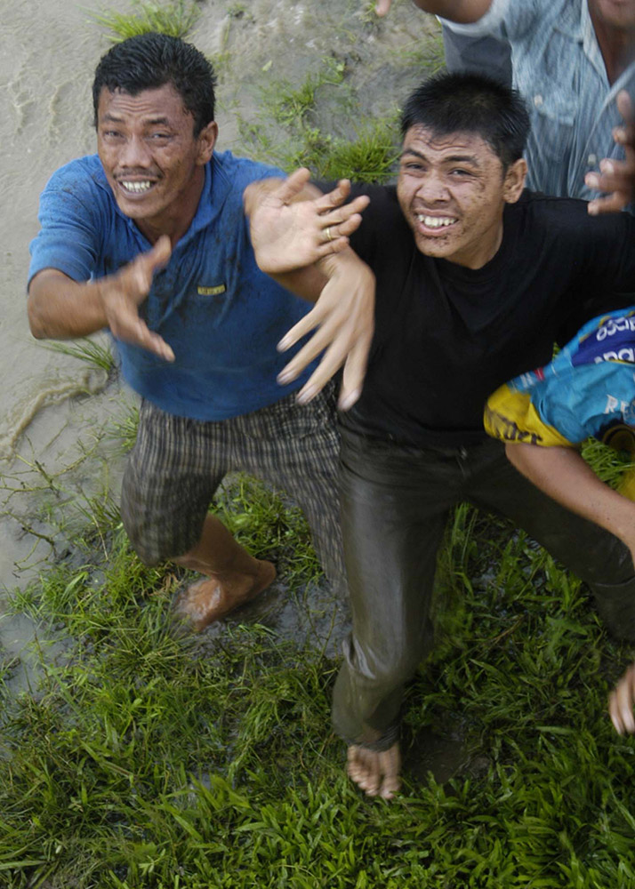 men-from-a-small-village-reach-to-catch-food-from-helicopter.jpg