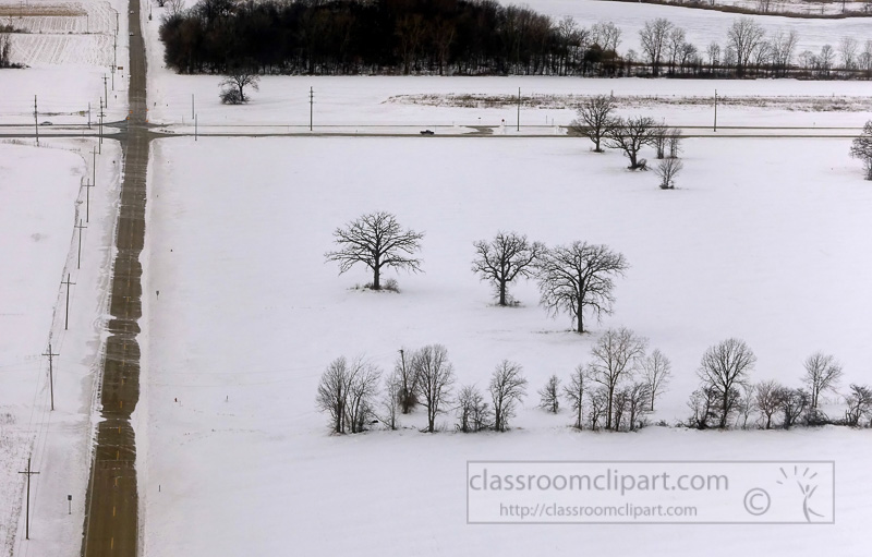 aerial view of snow covered country road with trees-.jpg